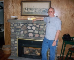 Jim stands in front of the fireplace at the cottage.  The Bliss-Daniells 1907 wedding picture hangs above the mantel.