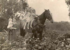 Iva holds Eleanor while Dora, Mary, and Betty ride the horse.